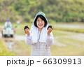田んぼでおにぎりを持つ女性 66309913