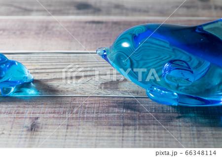木の板に置いた青いガラスのイルカ 66348114
