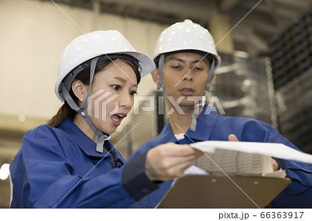 物流倉庫で在庫管理表を見て驚く作業員女性と指摘する作業員男性 66363917