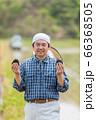 田んぼでおにぎりを持つ男性 66368505