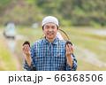 田んぼでおにぎりを持つ男性 66368506