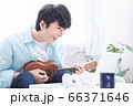 オンラインで楽器(ウクレレ)のレッスンを受ける若い男性 66371646