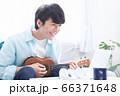 オンラインで楽器(ウクレレ)のレッスンを受ける若い男性 66371648