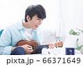 オンラインで楽器(ウクレレ)のレッスンを受ける若い男性 66371649