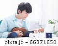 オンラインで楽器(ウクレレ)のレッスンを受ける若い男性 66371650