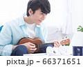 オンラインで楽器(ウクレレ)のレッスンを受ける若い男性 66371651
