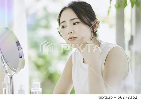 リビングでお肌のお手入れをする若い女性[悩んでいる] 66373362