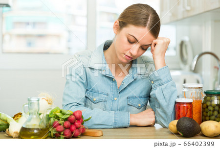 Woman suffering from headache at kitchen 66402399