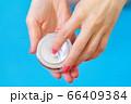 Woman holding hand cream on blue 66409384