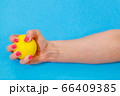 Woman squeezing yellow stress ball 66409385