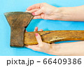 Woman touching old ax on blue background 66409386