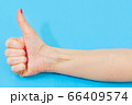 Woman showing thumbs up on blue 66409574
