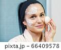 Woman using organic Konjac Cleansing Sponge for face 66409578