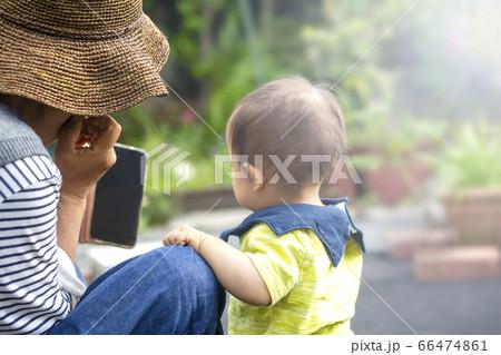 お庭でスマホを見ているおばあちゃんと孫の男の子 66474861