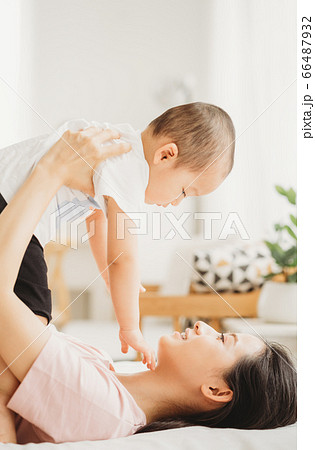 A woman lift up her son in the bed room 66487932