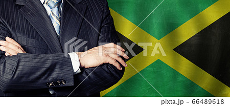 Male hands against Jamaican flag background, 66489618