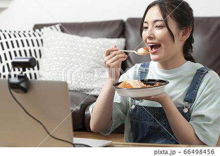 オンラインランチ会イメージ パソコンの画面を見ながらカレーを食べる若い女性 66498456