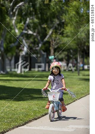 公園の歩道をサイクリングする笑顔の幼児(海外) 66519834