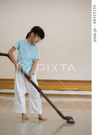 掃除機を使って部屋を掃除している空手クラブの子供 66524155