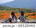 岩手県の三ツ石山の美しい紅葉を眺めながらお弁当を食べる二人の若い女性 66526464