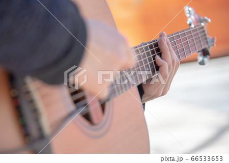 ストリートで演奏するミュージシャンのギター手元 66533653