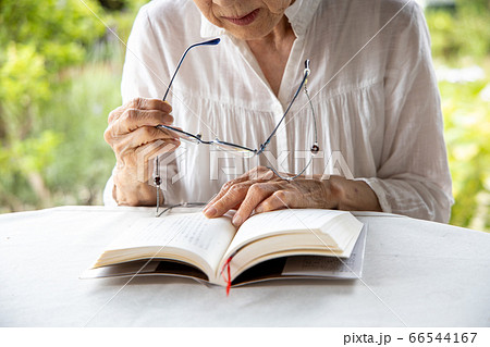 老眼鏡をもって読書しようとしている高齢女性 66544167