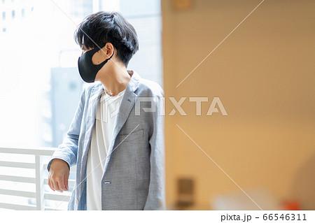 マンションのベランダで黒いマスクをつけてたたずむ若い男性 66546311