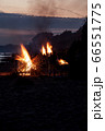 Unrecognisable people celebrating summer solstice with large bonfires on beach 66551775