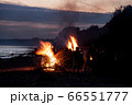 Unrecognisable people celebrating summer solstice with bonfires on beach 66551777