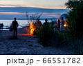 Unrecognisable people celebrating summer solstice with bonfires on beach 66551782