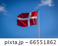 Danish flag in sunshine against blue sky with clouds, horizontal 66551862