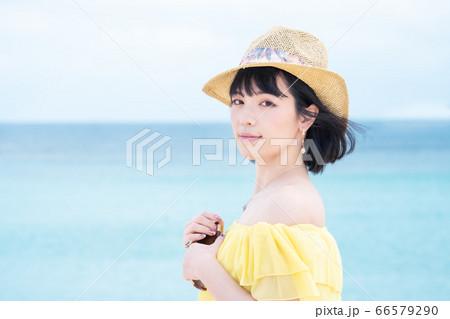 夏の海辺と笑顔の黄色いワンピースの女性 66579290