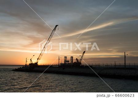 オレンジ色の夕暮れの空をバックに作業している海岸沿いのシルエットのクレーン 66600623