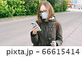 Student girl in a protective medical mask and glasses writes a text message, reads news, surfs the 66615414