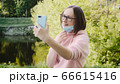 Trendy girl in a protective medical mask and glasses takes a selfie on a smartphone. 66615416