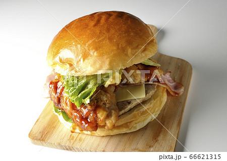 たっぷりのタレがしたたるベーコンとチーズとレタスとチキンがサンドされた大きいハンバーガー(白背景) 66621315
