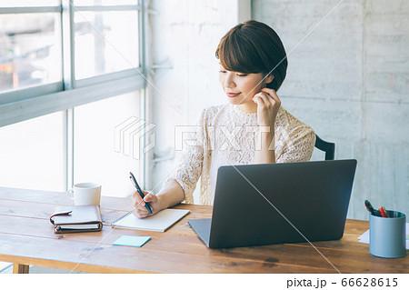 パソコンを見ながらメモを取る女性  66628615