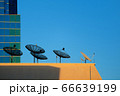 Satellite dish on top of a tall building 66639199