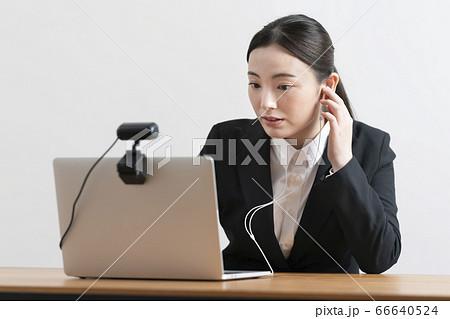 オンライン面接 パソコンの画面を見ながらヘッドホンをおさえるスーツ姿の女性 66640524