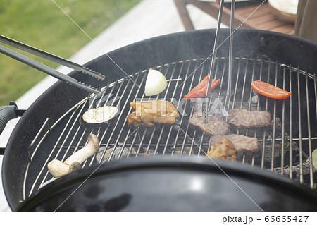 バーベキューコンロで肉を焼いている仕草(顔なし) 66665427