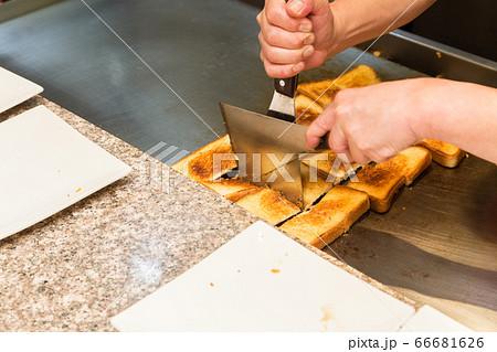 鉄板焼きレストランで食パンを切る手元 66681626