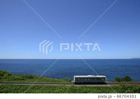山陰の海沿いを行くディーゼルカー 66704301