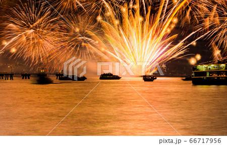 海上で特玉花火が打ち上げられています。真っ赤な海に人や船がシルエットになっています。広島 66717956