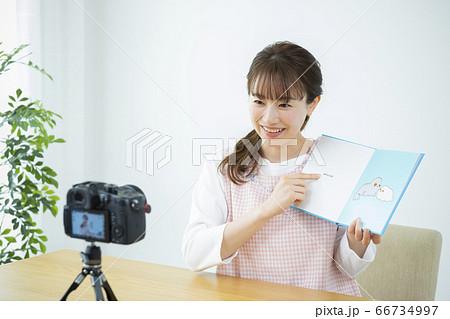 読み聞かせをする保育士(絵本はピクスタ撮影のために作成したダミーです) 66734997