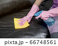 Woman wipe sofa with germicidal spray and wipe with towel. 66748561