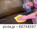 Woman wipe sofa with germicidal spray and wipe with towel. 66748567