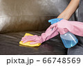 Woman wipe sofa with germicidal spray and wipe with towel. 66748569