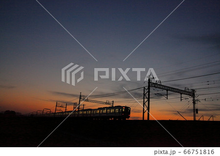 銅色に染めた夕焼けの中帰宅を急ぐ列車 66751816