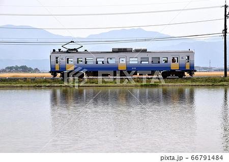 田植え前、水が張られた水田地帯を走るえちぜん鉄道 66791484