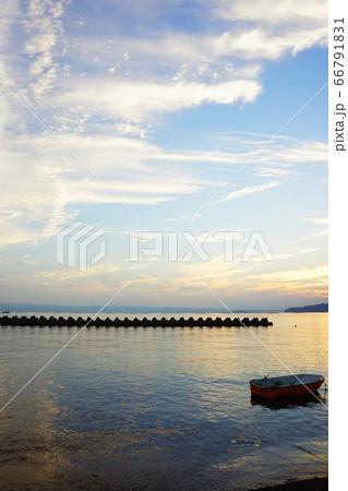 うっすらと焼けた空と穏やかな海に浮かぶ小舟 66791831